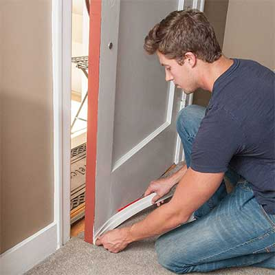 Man insulating a door with soundproofing material