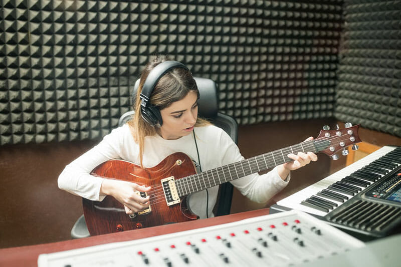 girl playing the guitar in a soundproof studio