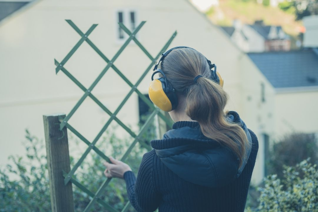 Woman with soundproof headphones measuring sound level of a garden fence